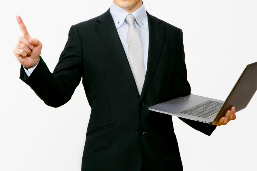パソコンを片手に指差しをする男性