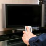 テレビとリモコンを持つ手