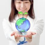 手のひらに地球のイメージ画像を載せた女性